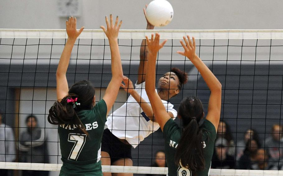 Ansbach's Caprice Lockett hits the ball over the Naples block of Victoria, left, and Isabel Krause in the Division II title match at the DODDS-Europe volleyball championships in Ramstein, Saturday. The defending champs beat Ansbach 23-25, 25-20, 25-17, 25-18.