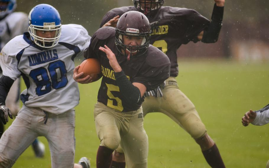 Baumholder's Ben Holliday looks downfield on his way to scoring a touchdown in the first half of play of the 2012 DODDS-Europe Division III football championship Saturday afternoon in Baumholder, Germany.