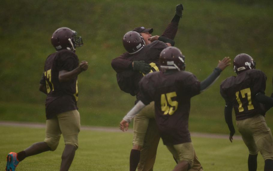 Baumholder's head coach, B.J. Walker celebrates with his team after defeating Rota 26-0 in the 2012 DODDS-Europe Division III football championship in Baumholder, Germany.