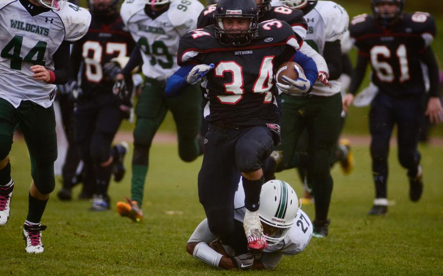 Bitgurg's Bryson Randall is tackled from behind by Naples' Howard Pulley Saturday evening in the 2012 DODDS-Europe Division II football championship in Baumholder, Germany. Bitburg edged Naples 22-20 to win its record fourth championship in a row.