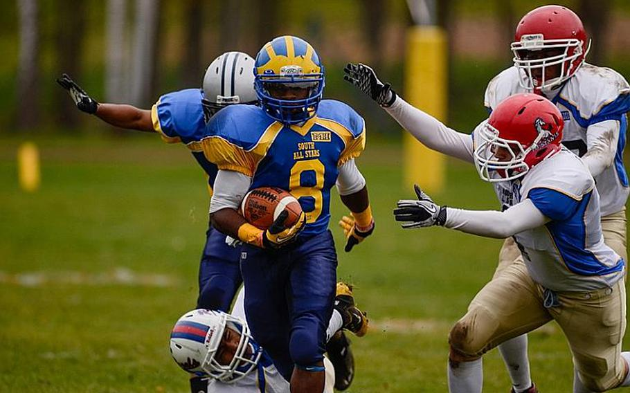 DODDS-Europe South All-Star football team member  Demar Flake of Ansbach High School breaks through a swarm of defenders Saturday afternoon in Vilseck, Germany as the South All-Stars defeated the North 29-10.