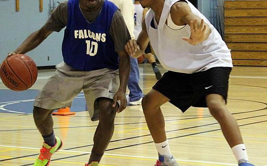 Junior Darien Briggs tries to dribble past senior Rashawn Wong during Tuesday's Seoul American Falcons boys basketball practice at Seoul American High School, South Korea.