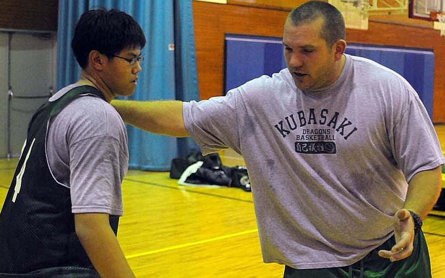 Kubasaki Dragons' seventh-year head coach Jon Fick positions senior Darwin Eusebio defensively during Thursday's practice at Marine Corps Air Station Futenma, Okinawa. Fick has won three Far East Division I Tournament titles, the first DODDS coach to reach three in a seven-season span.