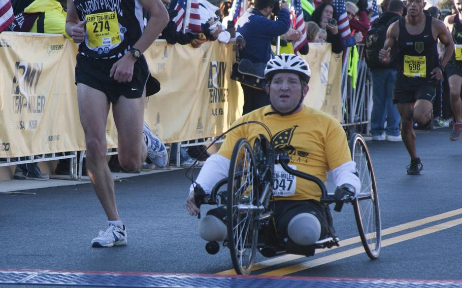 A wounded warrior crosses the finish line of the 29th annual Army 10-Miler race outside the Pentagon on Oct. 20, 2013.