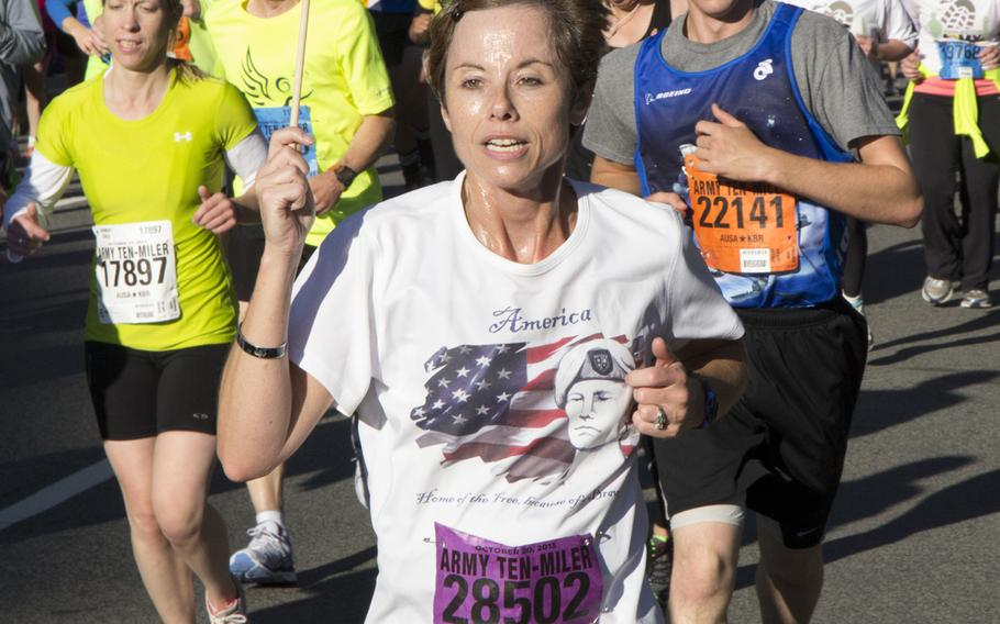 Ruby Silvey of Simpsonville, S.C. carries a flag during the Army 10-Miler, Oct. 20, 2013 in Arlington, Va. and Washington, D.C.