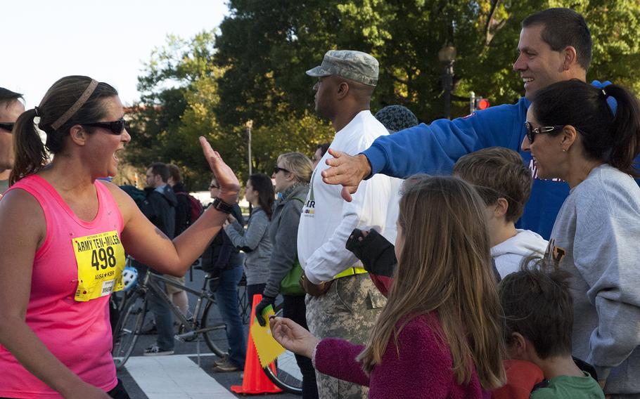 Sarah Luebbert of Elizabethtown, Ky. high-fives a spectator at the Army 10-Miler, Oct. 20, 2013, in Arlington, Va. and Washington, D.C.