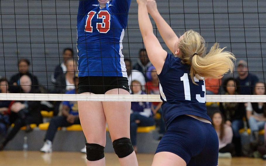 Ramstein's Sarah Schiller, left, flies high to try and block ashot by Lakenheath's Shannon Cox in the championship match at the DODDS-Europe volleyball finals in Ramstein, Germany, Nov. 2, 2013. Ramstein beat Lakenheath 25-18, 25-20, 25-19 to take their third straight Division I title. Schiller was named the Division I tourney MVP for the second straight year.