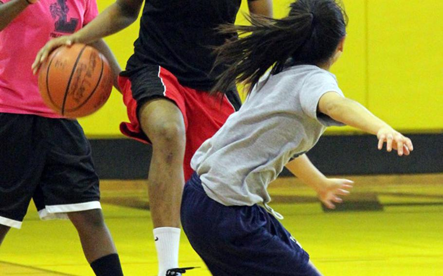 """Kadena junior Jasmine Rhodes, with ball dribbling against teammates Jordan Micko and Aira Shankles, is considered one of the more complete players in the Pacific, longtime Kubasaki coach Robert Driggs said. """"She does everything but sell popcorn,"""" Driggs remarked."""