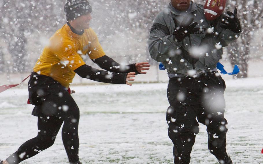 Army Staff Sgt. Elvin Thomas juggles the football as Navy Lt. Cmdr. Jason Zaharris goes for Thomas' flag during Friday's Army-Navy flag-football rivalry game at Misawa Air Base, Japan. Naval Air Facility Misawa beat the Army's 708th Military Intelligence Detachment 27-0 in a game played in wind-blown snow with temperatures around freezing.