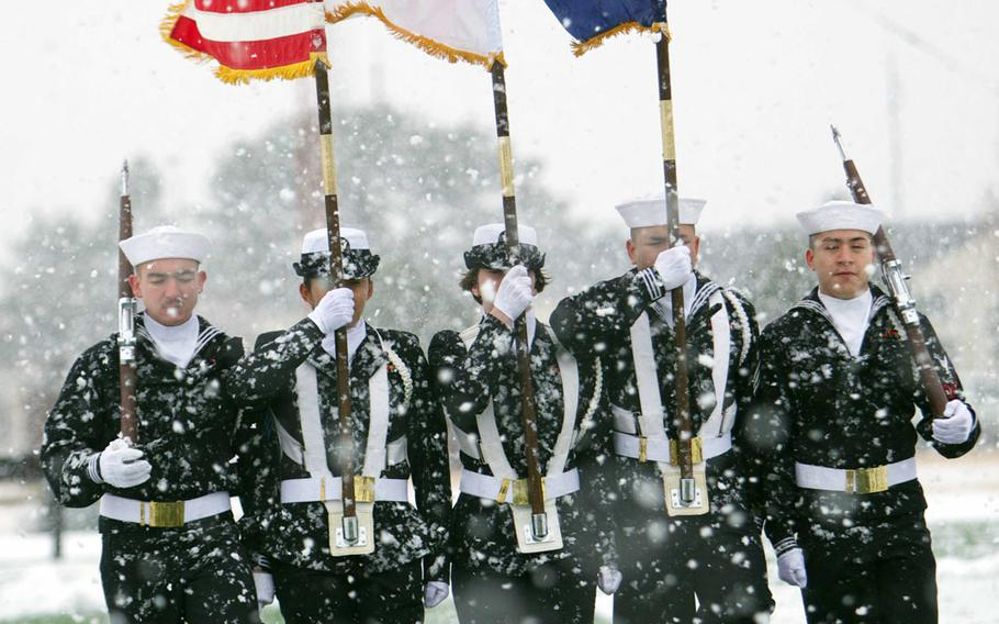 A Navy honor guard brings the colors onto the field prior to Friday's Army-Navy flag-football rivalry game at Misawa Air Base, Japan. Naval Air Facility Misawa beat the Army's 708th Military Intelligence Detachment 27-0 in a game played in wind-blown snow with temperatures around freezing.
