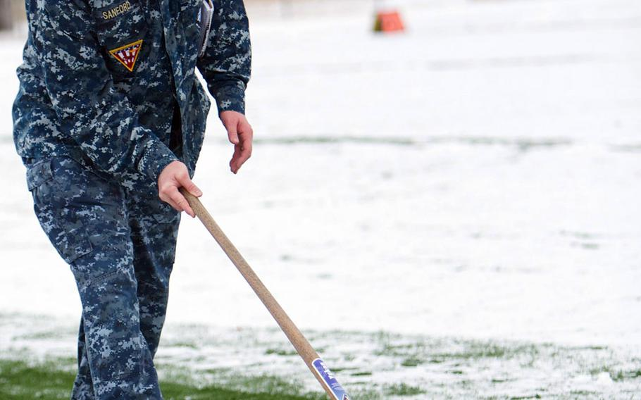 Navy Master Chief Petty Officer Daniel Sanford of NAF Misawa public affairs shovels snow off the field prior to Friday's Army-Navy flag-football rivalry game at Misawa Air Base, Japan. Naval Air Facility Misawa beat the Army's 708th Military Intelligence Detachment 27-0 in a game played in wind-blown snow with temperatures around freezing.