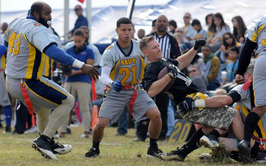 Navy's Joe King and Howard Gomez close in on Army running back Brent Owens during Saturday's 24th Army-Navy flag-football rivalry game at Torii Station, Okinawa. Army rallied to win 27-15.