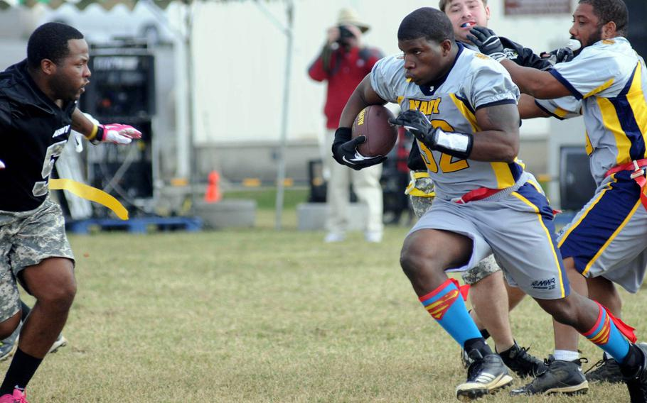Navy running back Quentin Foley charges toward Army defender Brandon Hunter during Saturday's 24th Army-Navy flag-football rivalry game at Torii Station, Okinawa. Army rallied to win 27-15.