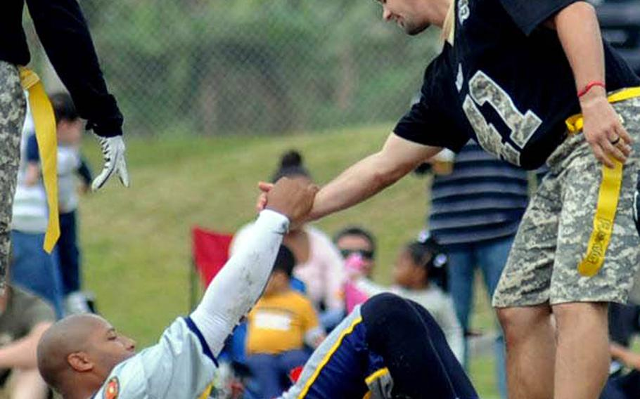 Army defender Drew Majors helps Navy quarterback Sanford James to his feet during Saturday's 24th Army-Navy flag-football rivalry game at Torii Station, Okinawa. Army rallied to win 27-15.