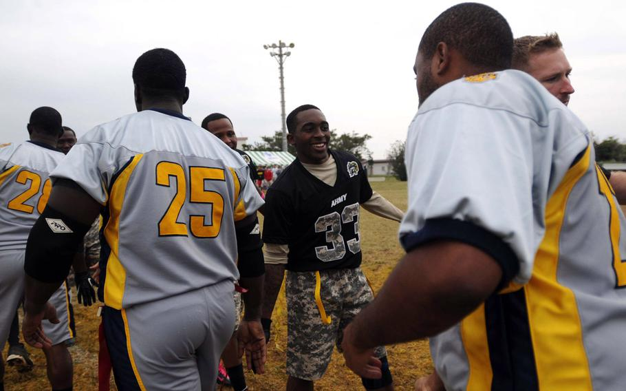 Army's Gerhon Teague and his teammates accept congratulations from the Navy side after Saturday's 24th Army-Navy flag-football rivalry game at Torii Station, Okinawa. Army rallied to win 27-15.