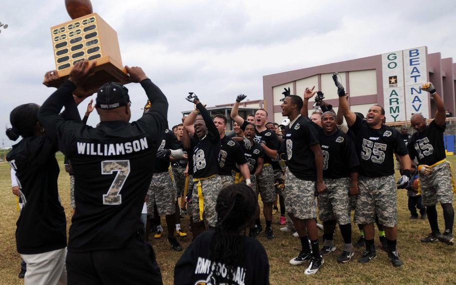 Army Col. Sheila Bryant and Sgt. Maj. Shelton Williamson, Torii Station's commanding officer and command sergeant major, hold the Commanders Trophy aloft while Army's players cheer after their 27-15 come-from-behind win over Navy in the 24th Army-Navy flag-football rivalry game at Torii Station, Okinawa.