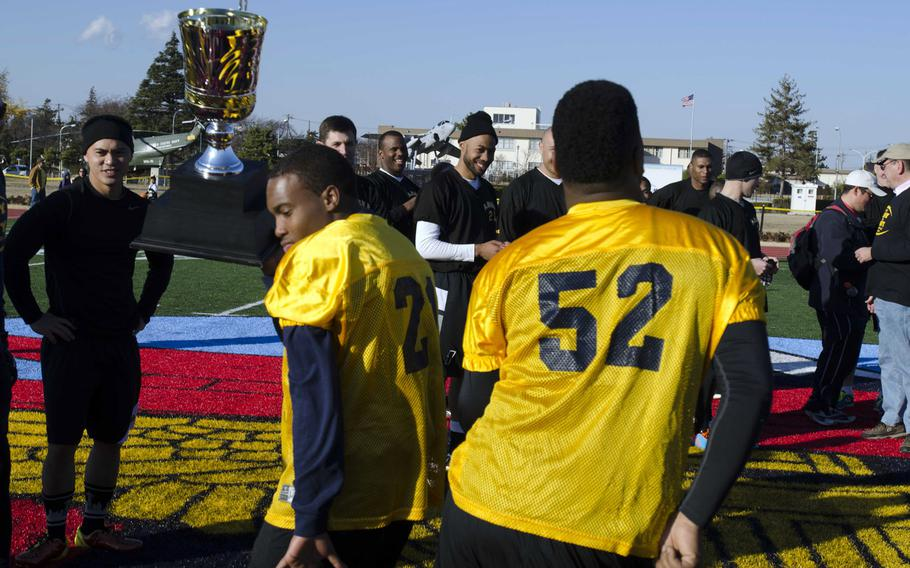 Navy players celebrate with the trophy following the annual Army-Navy flag football game Saturday at  Naval Air Facility Atsugi, Japan. Navy led 13-0 at half and hung on to win 13-12.