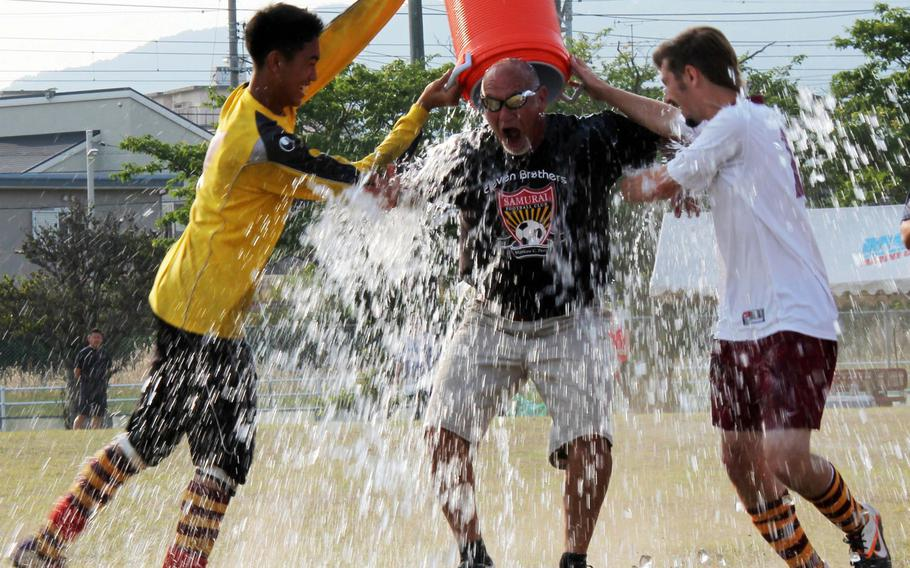 Matthew C. Perry Samurai boys soccer coach Mark Lange gets the water-bucket treatment from Sam Cadavos and Robert Whiteside after the Samurai captured their third Far East Division II Tournament title in five years and second in a row.