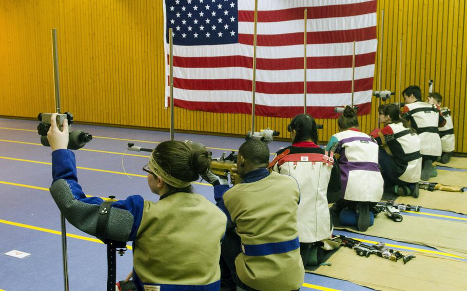 Varsity shooters from Wiesbaden, Kaiserslautern and Baumholder prepare to fire from the kneeling position during a conference marksmanship competition in Wiesbaden, Saturday, Jan. 21, 2017.