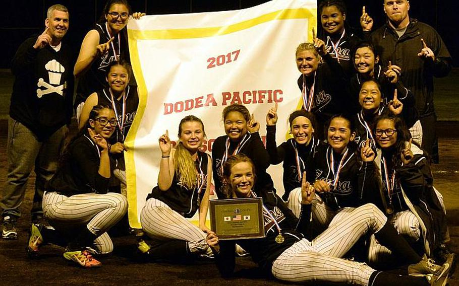 Zama players and coaches gather round the banner after beating Yokota 13-3 in the third of three Far East Division II Softball Tournament final games on Wednesday.  DAVE ORNAUER/STARS AND STRIPES
