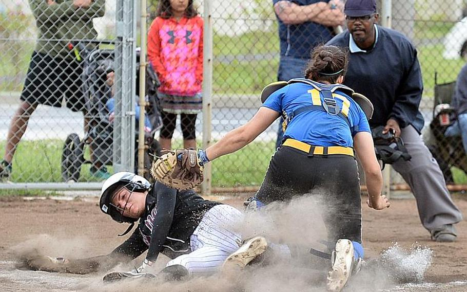 Zama's  Ally Chiarenza gets tagged out by Yokota catcher Irene Diaz during Wednesday's final games in the Far East Division II Softball Tournament. Yokota won the first two 16-0 and 10-6 before Zama prevailed 13-3 in the third game for the Trojans' first title since 2012.  DAVE ORNAUER/STARS AND STRIPES