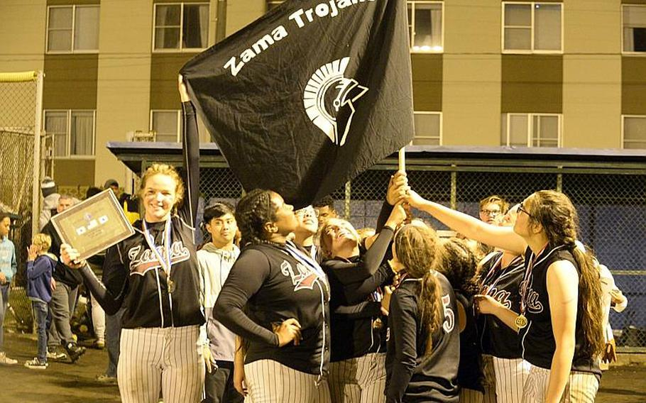 Zama players gather round a flag emblematic of their school after beating Yokota 13-3 in the third of three Far East Division II Softball Tournament final games on Wednesday.  DAVE ORNAUER/STARS AND STRIPES