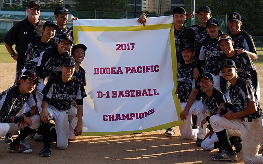 American School In Japan players and coaches gather round the banner after beating Kadena 5-4 for the Mustangs' fourth straight Far East Division I Baseball Tournament title.  WESTON GRAVES/SPECIAL TO STRIPES
