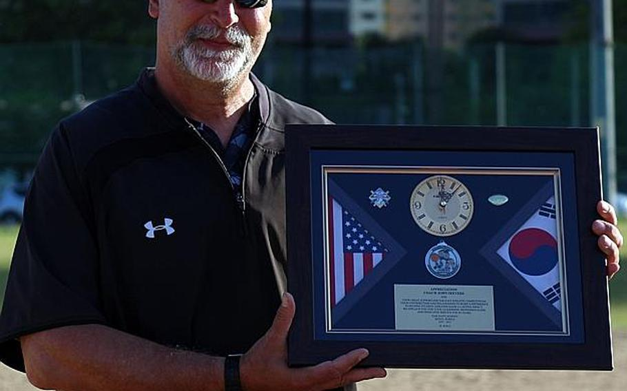 American School In Japan coach John Seevers displays a farewell gift given to him after his Mustangs beat Kadena 5-4 for their fourth straight Far East Division I Baseball Tournament title. Seevers is retiring after 40 years at ASIJ.  WESTON GRAVES/SPECIAL TO STRIPES