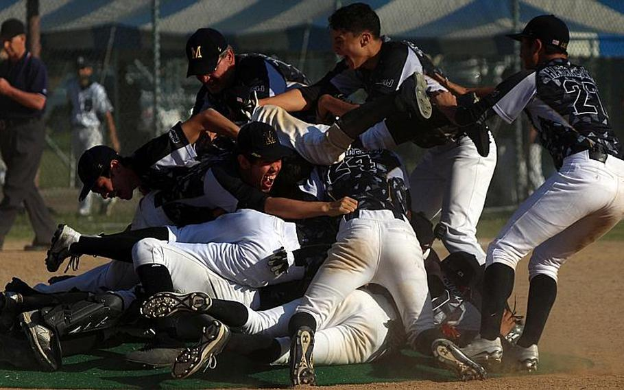 American School In Japan players dogpile on the mound after beating Kadena 5-4 for the Mustangs' fourth straight Far East Division I Baseball Tournament title.  WESTON GRAVES/SPECIAL TO STRIPES