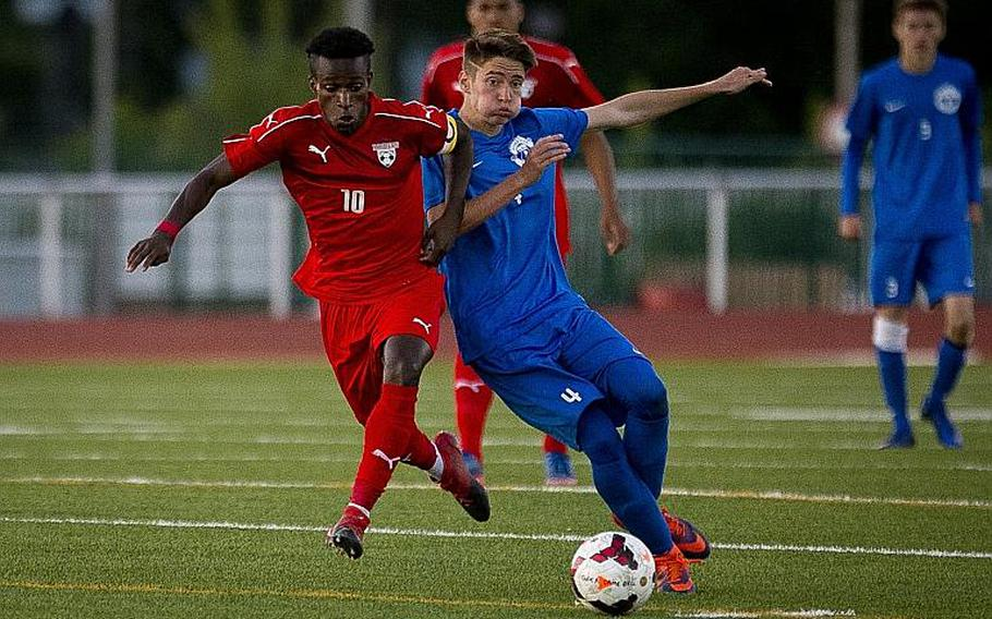 Kaiserslautern's Alexander Dexter, left, and Ramstein's Gavin McMillan race for the ball during the DODEA-Europe Division I championship in Kaiserslautern, Germany, on Saturday, May 20, 2017. Kaiserslautern won the title match 3-1.