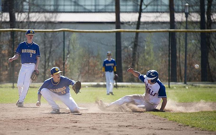 Ramstein's Kyle Glenn slides into second base as Wiesbaden's Damian Pinion, center, waits for the throw and Finn Swafford watches the play at Ramstein Air Base, Germany, on Thursday, March 30, 2017.