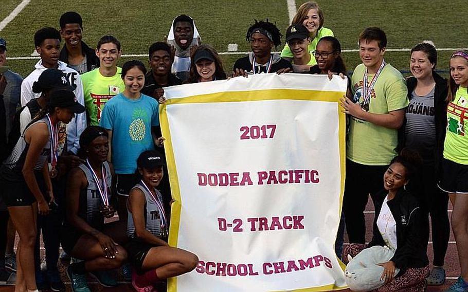 Zama athletes and coaches gather round the banner after the Trojans won their fourth straight Far East Division II track and field school championship.  DAVE ORNAUER/STARS AND STRIPES