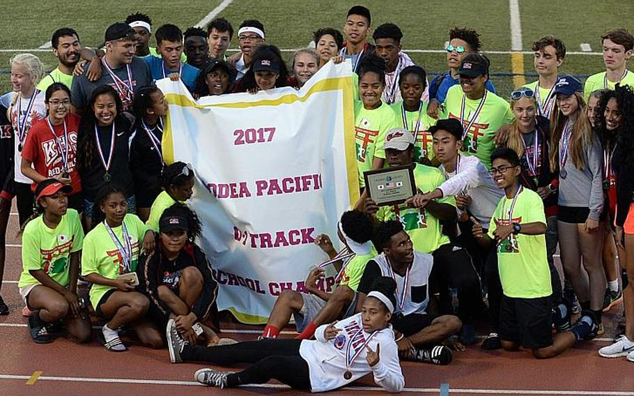 Nile C. Kinnick athletes and coaches gather round the banner after the Red Devils won their third straight Far East Division I track and field school championship.  DAVE ORNAUER/STARS AND STRIPES