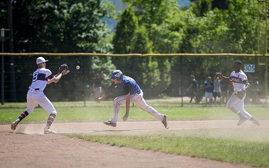 Sigonella's Alex Ogletree dives to get out of a pickle between Bitburg's Max Little, left, and Jermaine Cooks Jr. during the DODEA-Europe Division II/III baseball championship at Ramstein Air Base, Germany, on Saturday, May 27, 2017. Sigonella won the game 10-1.  MICHAEL B. KELLER/STARS AND STRIPES