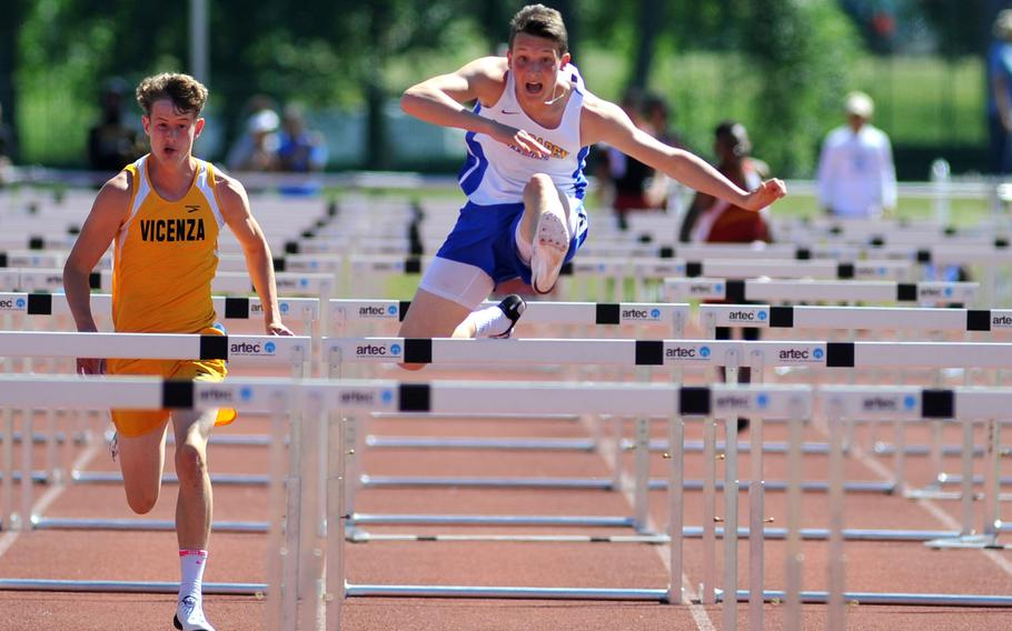 Wiesbaden's Garrett Armel clears a hurdle on his way to winning the 110-meter event in 15.82 seconds at the DODEA-Europe track and field finals in Kaiserslautern, Germany, Saturday, May 27, 2017. At left is Vicenza's Dawson Merkel who came in second.