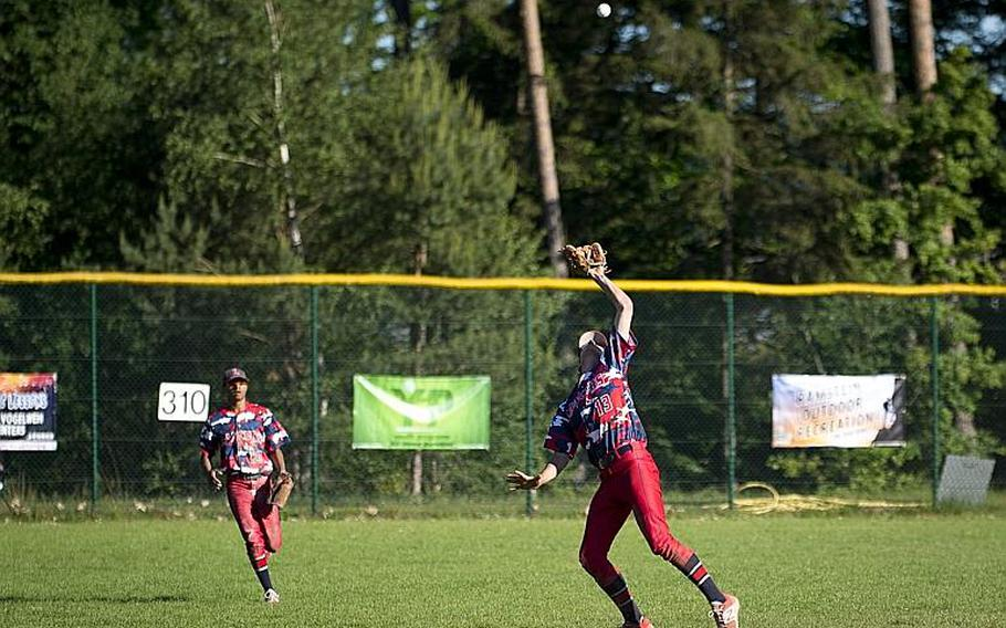 Lakenheath's Michael Nighbert, right, catches a fly ball as Jordan Harris moves in to assist during the DODEA-Europe Division I baseball championship at Ramstein Air Base, Germany, on Saturday, May 27, 2017. Lakenheath lost the game against Ramstein 8-6.  MICHAEL B. KELLER/STARS AND STRIPES