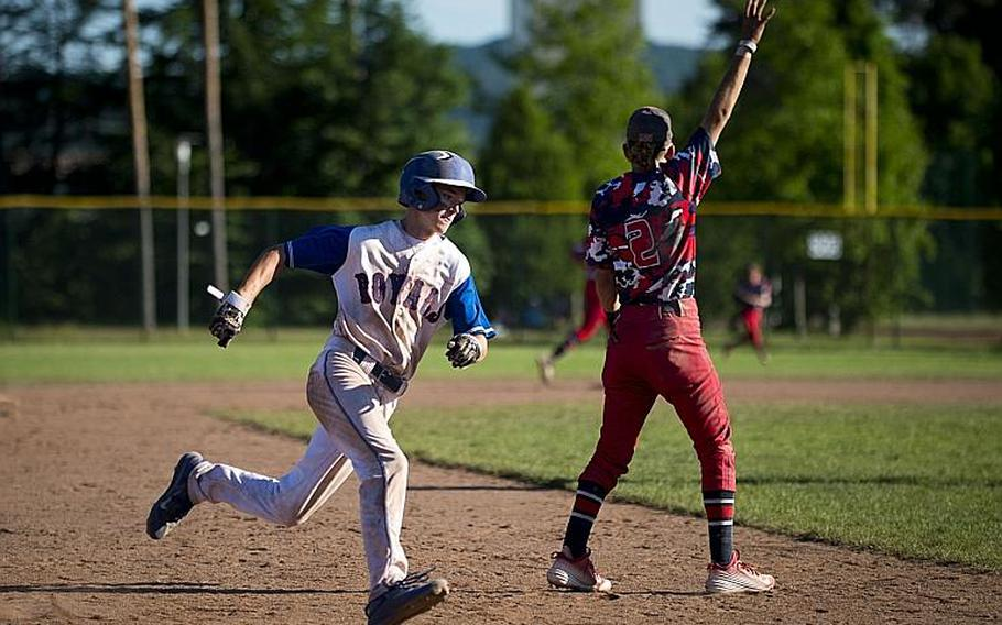 Ramstein's Reed Marshall rounds third behind Lakenheath's Kaiden Morales during the DODEA-Europe Division I baseball championship at Ramstein Air Base, Germany, on Saturday, May 27, 2017. Ramstein won the game 8-6.  MICHAEL B. KELLER/STARS AND STRIPES