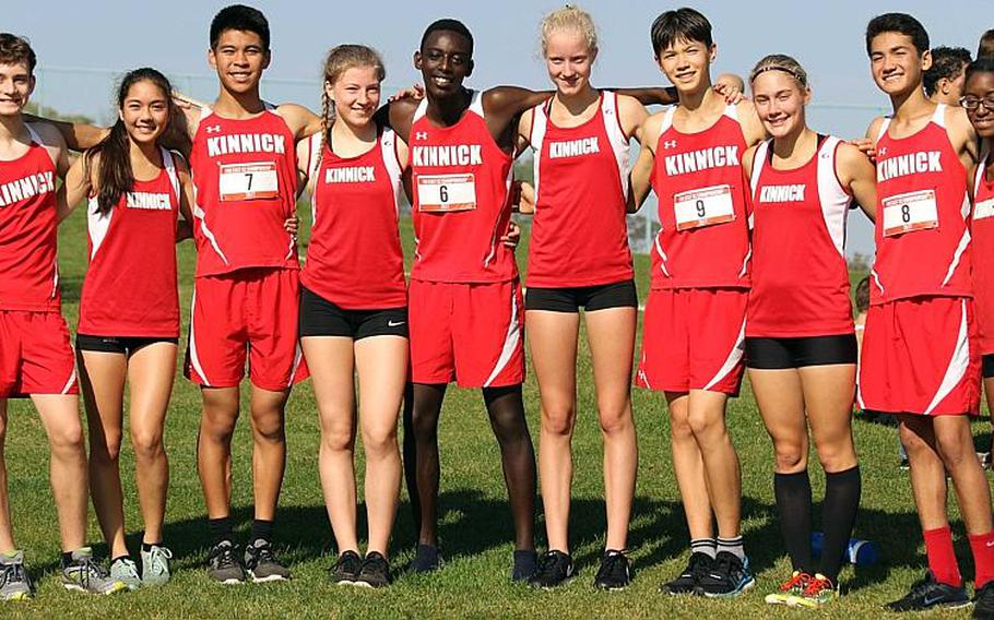 A Red Devil of a repeat. Nile C. Kinnick's cross country team arm in arm after capturing its second straight Far East cross-country Division I overall school banner, the second time in 10 years.