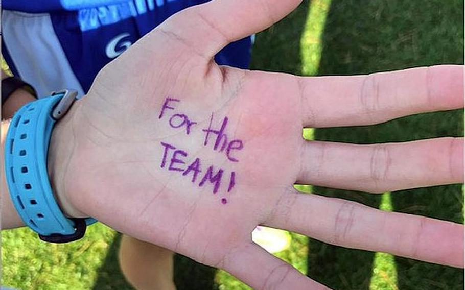 """Seoul American runners wrote on their left hands """"For The Team!"""" prior to Thursday's Far East cross country team relay. Seoul American's Tucker Chase and Chloe Byrd crossed the finish line first."""