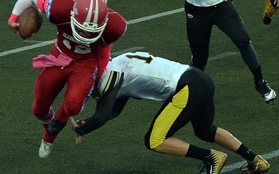 Nile C. Kinnick quarterback Kacey Walker tries to evade the tackle of Kadena's Owen Sinning.