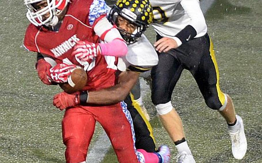 Nile C. Kinnick's Devoney Stanley nearly loses the football as he's wrapped up by Kadena's Eric McCarter.