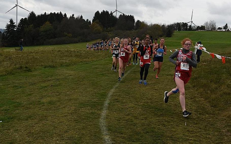 Runners spread out as they race down a hill and around a bend at the Rolling Hills Golf Course in Baumholder, Germany, on Saturday, Oct. 28, 2017. The wind and cold made race conditions challenging at the DODEA European cross country championships.