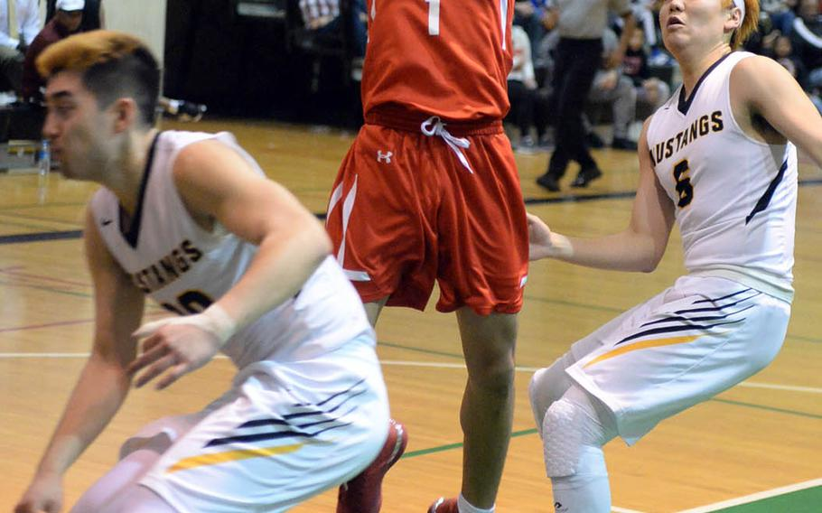 Nile C. Kinnick's Rashad Rapada drives between American School In Japan's Koki Wiley and Ray Shino during Tuesday's final in the Far East Boys Division I Basketball Tournament. The Red Devils routed the Mustangs 75-50 for the first tournament title in Kinnick school history.