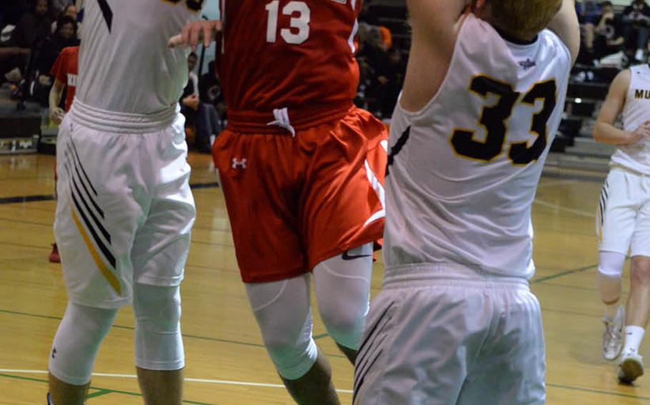Nile C. Kinnick's Kedrick Stockman pulls up between American School In Japan's Koki Wiley and Oliver Rogers during Tuesday's final in the Far East Boys Division I Basketball Tournament. The Red Devils routed the Mustangs 75-50 for the first tournament title in Kinnick school history.