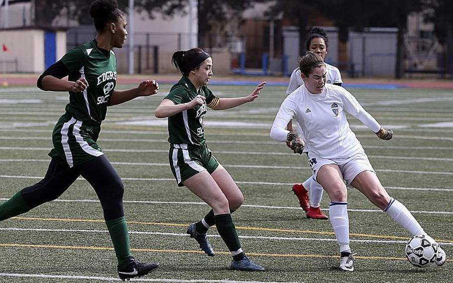 Junior Caleigh Garcia, dribbling against Robert D. Edgren's Christina Taylor and Abigail Gomez, is one of a handful of new key strikers for Yokota girls soccer.