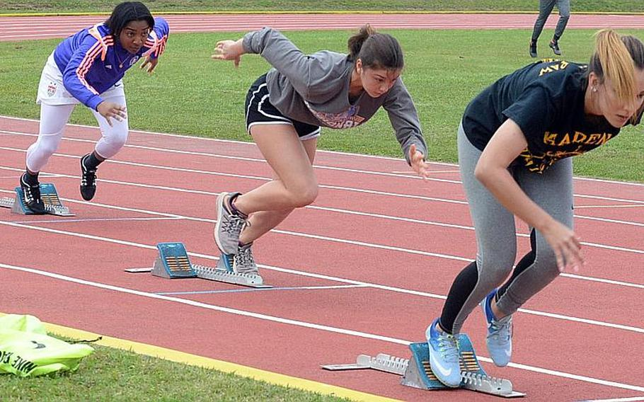 Kadena hurdlers, from left, Rhamsey Wyche, Sofia Strawder and Crystal Scott charge out of the starting blocks.