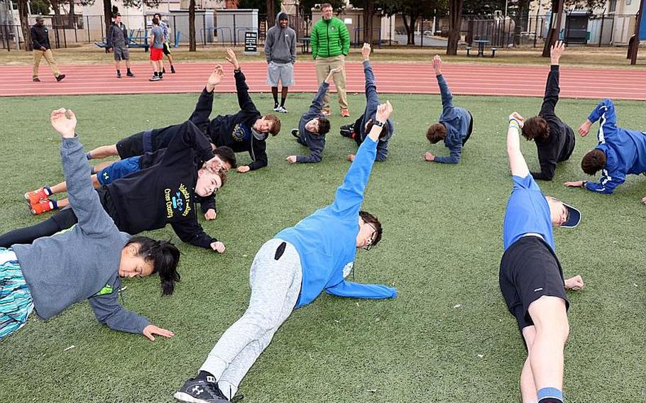 Yokota track and field athlletes warm up under the watchful eye of coach Dan Galvin, background.
