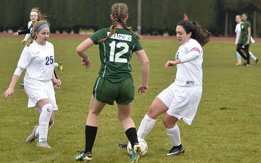 Alconbury???s Allison Diamond tries to defend against Brigands Carmen Beckley, right, and Hayden Sink, left, during a high school varsity soccer game at RAF Alconbury, England, Saturday, March 24, 2018. The Dragons won 3-2 against the Brigands.