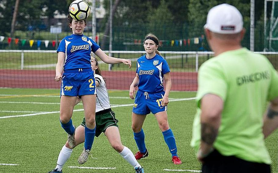 Sigonella's Cecelia Warren, left, heads the ball over Alconbury's Isabel Black as fellow Jaguar Emily Havard watches during the DODEA-Europe Division III soccer championship in Kaiserslautern, Germany, on Thursday, May 24, 2018.