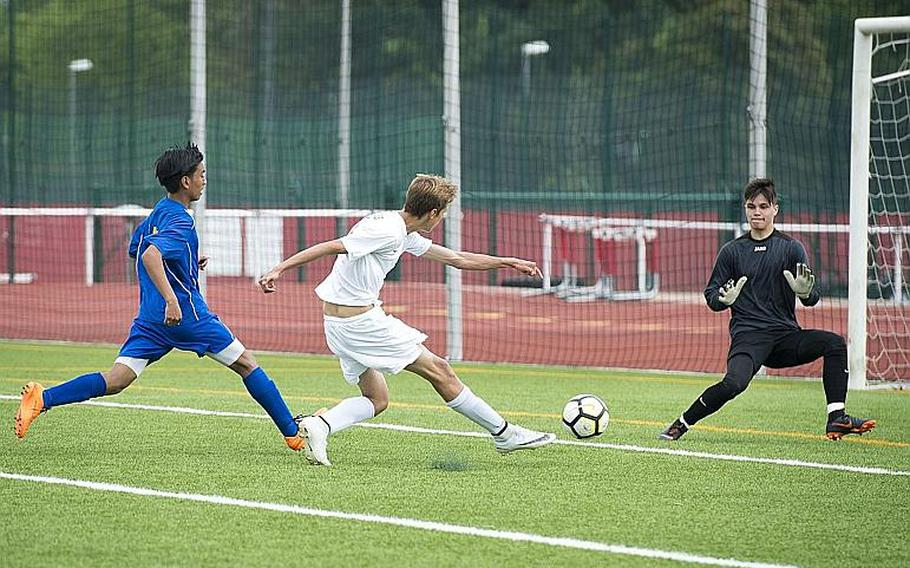 Brussels' Ben Gray takes a shot on Ansbach's Nick Benson, right, as Rommel Sebastian Penaflor drops back to assist during the DODEA-Europe Division III soccer championship in Kaiserslautern, Germany, on Thursday, May 24, 2018. Brussels won the game 7-0.